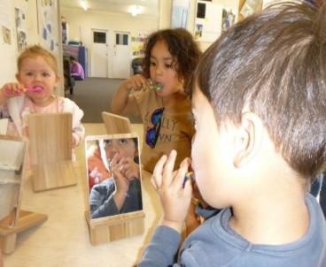 Three children brushing their teeth