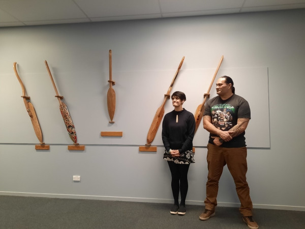 Two people stand in front donated Kauri timbers.