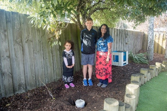 Two children and adult preparing to dig up time capsule