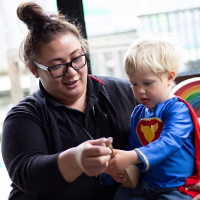 Verneese Ioane sits with a child in an early childhood learning centre